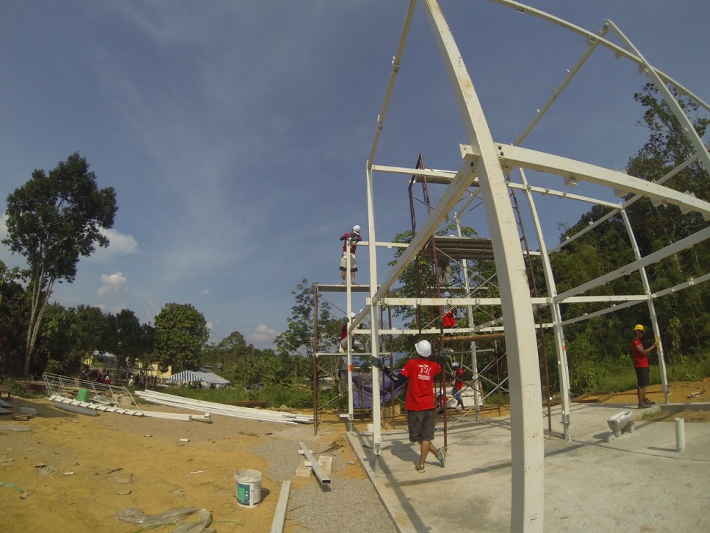 The steel frame of a two-storey jungle cabin being bolted into position