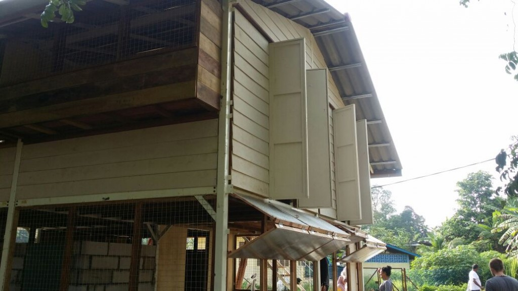 This Malaysian jungle cabin has French windows and wire netting windows over the storage bench