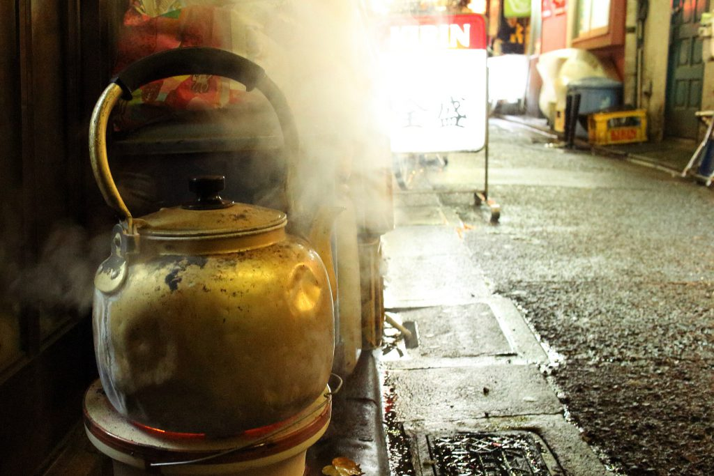 An old battered kettle boiling water on a side-street