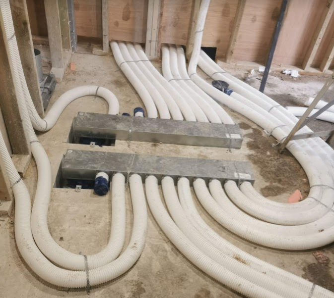 Manifolds for a radial semi-rigid ductwork system mounted on concrete floor