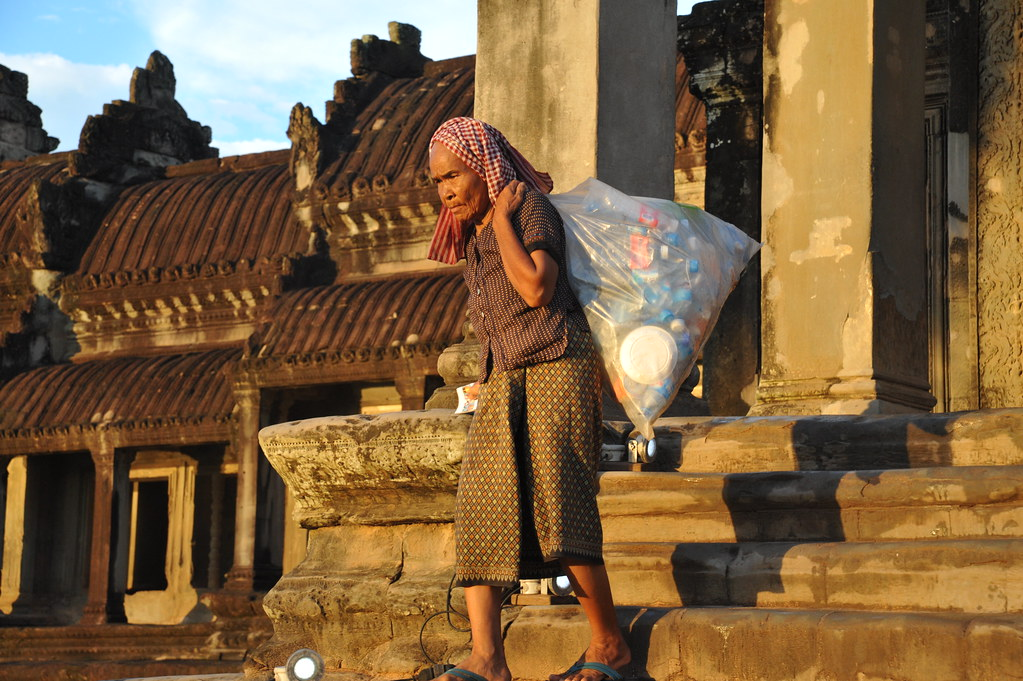 Old lady collects plastic bottles in Indonesia