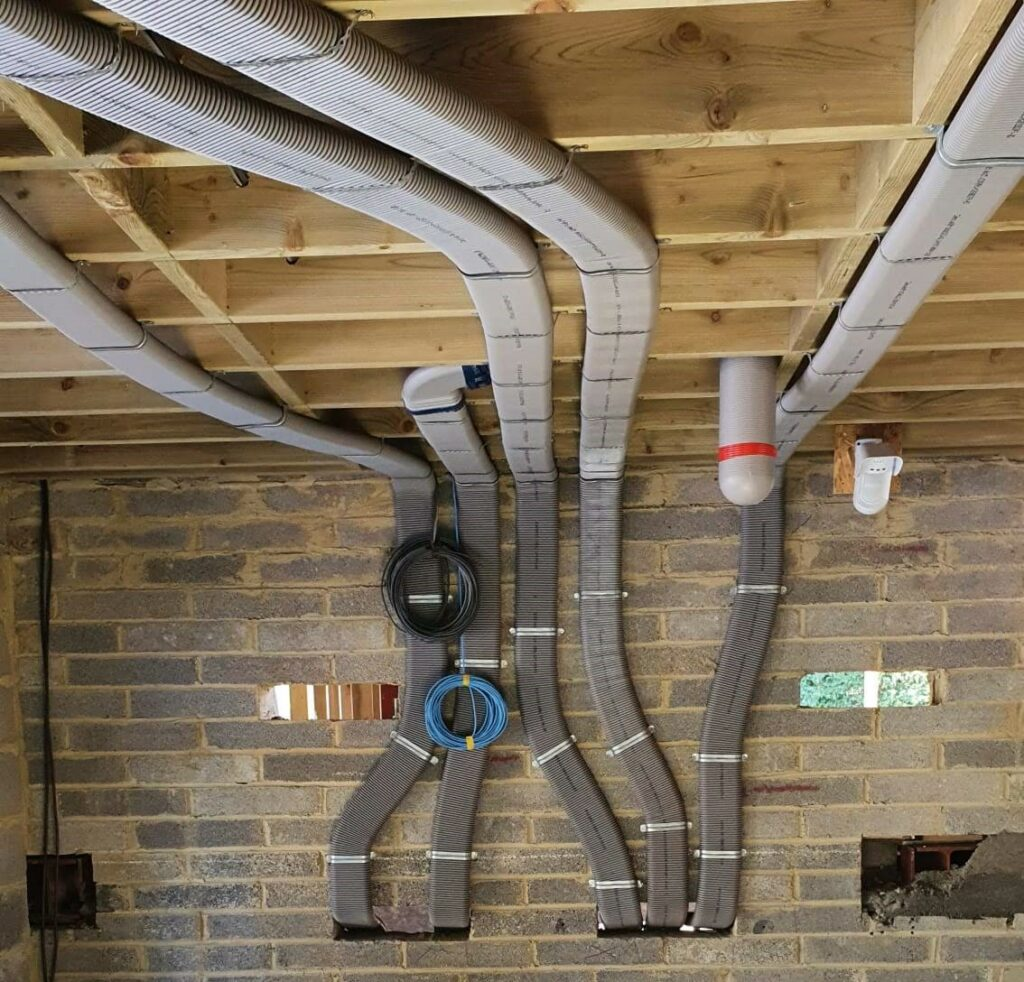 Flat 51mm ducting pinned to wall and rising into ceiling area