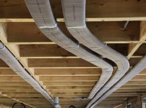 Flat 51mm semi-rigid ducting running pinned neatly to ceiling joists to prevent loss of room height