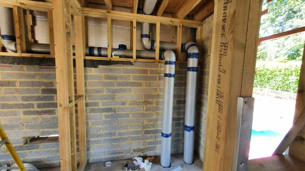 Preinsulated ducting running from basement to roof behind fitted wardrobe frame