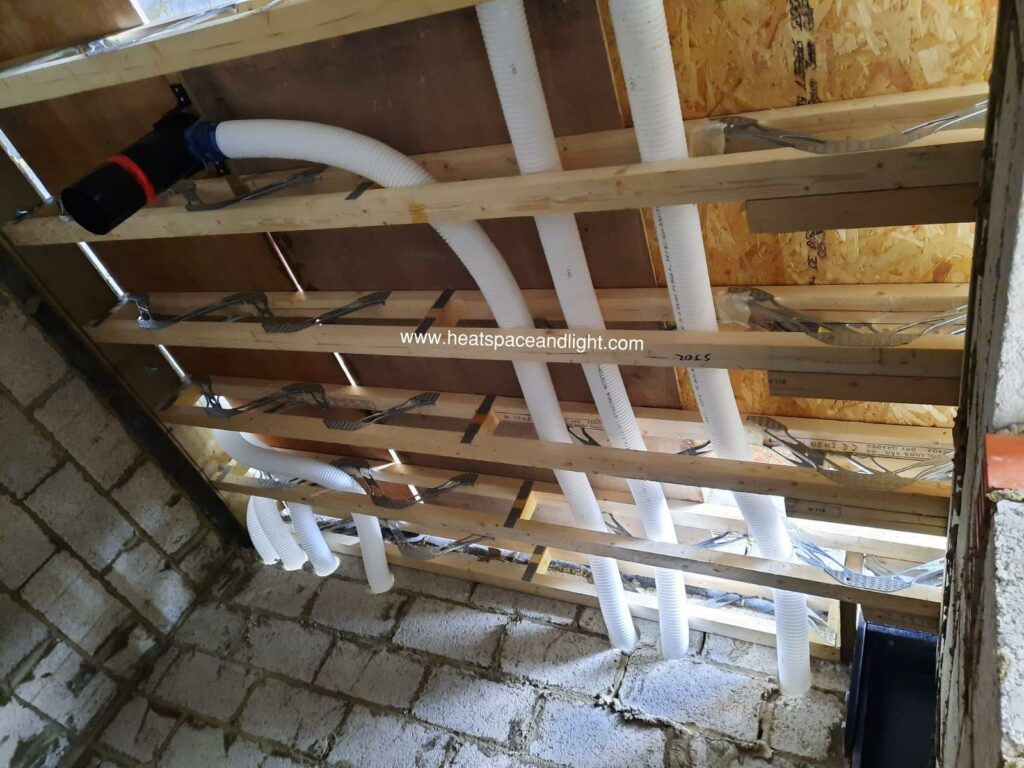 90mm semi-rigid ducting in webbed joists and passing through core-drilled blockwork wall for MVHR system